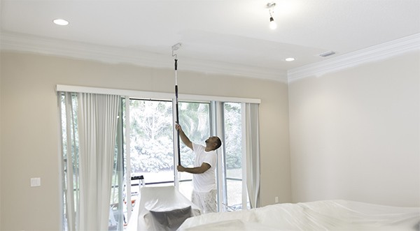 Painter using a roller to paint the ceiling